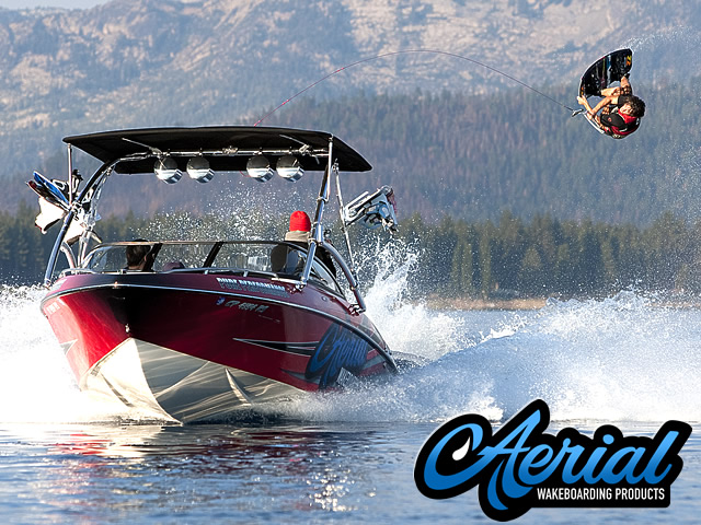Photo of wakeboarder using a Aerial Assault Wakeboard Tower with Integrated Navigation LED Light - Polished Aluminum with 2 Wakeboard Tower Racks
